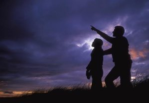 father and daughter silhouetted against dusk sky looking up at stars, United Kingdom, Scotland, Wester Ross